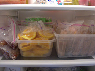Make ahead lunch ideas stored in a refrigerator. Bins of oranges, grapes, and sandwiches individualy stored in plastic baggies.
