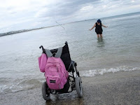 Wheelchair on beach with woman in the ocean behind (photo by Neil Marcus)