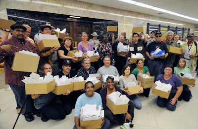 28 people holding 18 boxes of letters inside the state capital building.