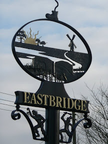 On the left is Eastbridge Village sign. On the right a view looking towards the Minsmere Toll Bridge, locally known as the Tu Penny bridge