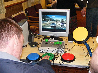 Image of a man using a large AbleNet green button to make a car go in BurnOut Paradise on the Xbox 360. Off screen he is assisted by someone steering using a conventional controller.