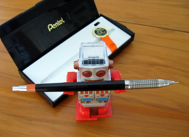 Pentel Mechanica mechanical pencil and case, carried by robot