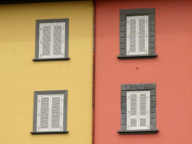 White window shutters on pink and yellow walls, Livorno