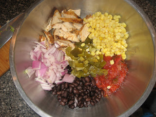 large silver bowl with chicken, diced red onions, black beans, pickled jalapeno, tomatoes, and corn