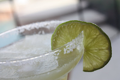 glass with margarita and salted rim served with a lime slice