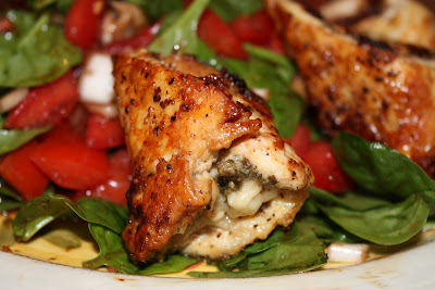 close up of one pesto chicken roll laying on spinach salad