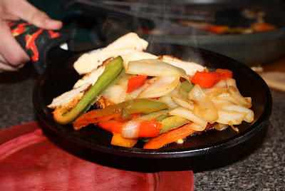 hand holding skillet with chicken, bell peppers, and onions