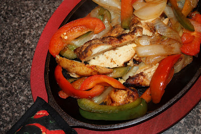 skillet with cooked chicken, red and green bell peppers, and white onions