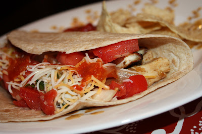 tortilla folded over with chicken, onions, bell peppers, diced tomatoes, cheese, and hot sauce
