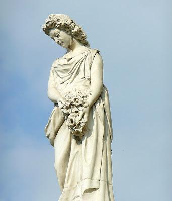 Estatua de mujer de pié con ramo de flores sobre su regazo.