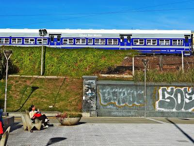 Persona sentada detras suyo pasa el tren.