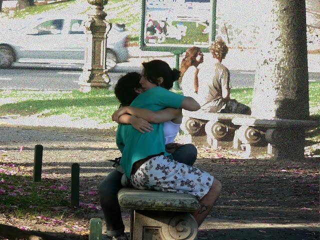 Pareja de enamorados abrazados en banco de plaza.