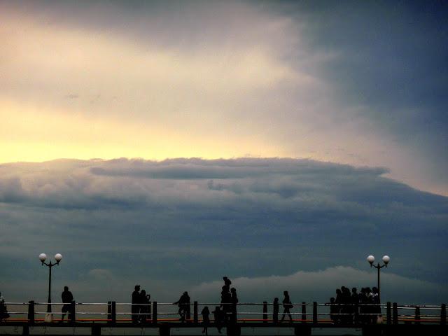 Paisaje costero con nubes y gente en la rambla.