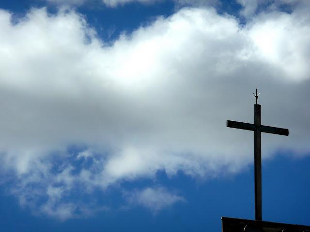 Una cruz y nubes adorándola.
