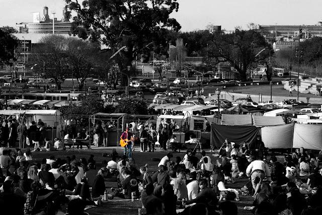 Paisaje urbano, gente en Recoleta escuchando a un cantor.