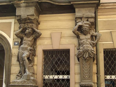 statues next to window of house in Prague