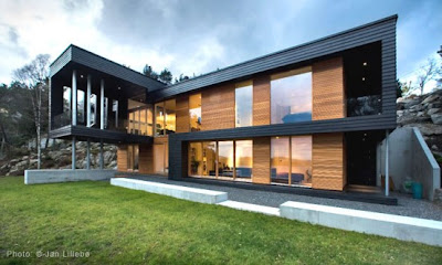 Modern Twofold House In Black Stained Wood With Natural Wood Between The Window Partitions