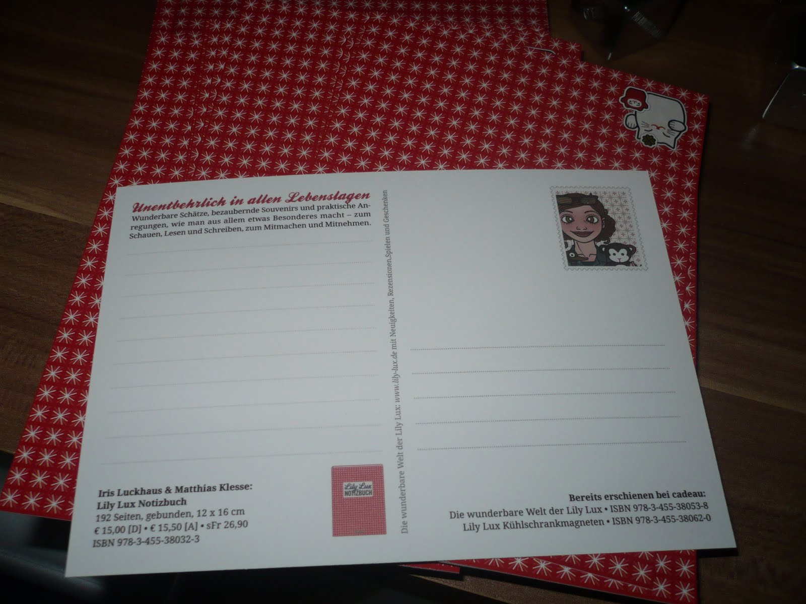 Foto von den Postkarten zum Lily Lux Notizbuch mit einem Passbild mit Äffchen als Briefmarke