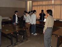 カーテンを閉めた教室でアイマスクをした参加者が立って話を聞いている様子