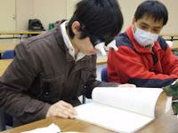 視野狭窄のシュミレーション眼鏡で本を読んでいる参加者