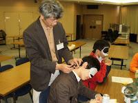 安全な筒を使って参加者にお灸をすえる講師