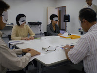 アイマスクをしてテーブルをかこむ参加者