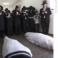 Mourners pray over bodies of Rabbi Gavriel Noach Holtzberg and his wife,