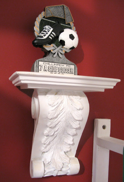 hanging awards on a corbel on a red kid's room wall | funkyjunkinteriors.net