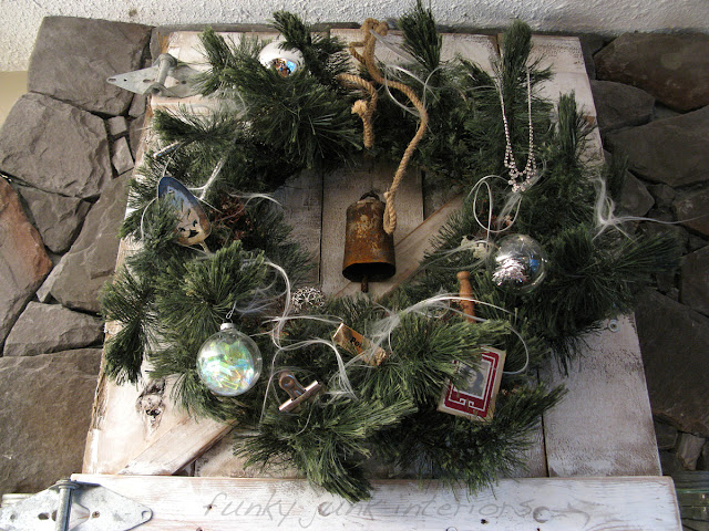 Faux Christmas wreath decorated with junk and angel hair hanging on a rustic gate.