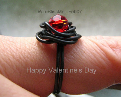 Wire wrapped rose ring with black steel wire and red crystal focal