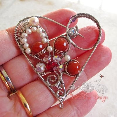 Holding the wire wrapped Heart brooch with pearl, agate and swarovski crystals