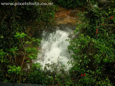 small waterfalls closeup photograph photographed from a small stream of water in munnar hills kerala