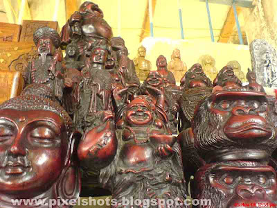 sculptures made in clay,lord buddha etc are sculptured and put for sale in street shop in mattancherry cochin