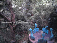 men sculptures in conference around a candle flame,sculpture park of thenmala,leisure zone sculpture photos of thenmala ecotourism