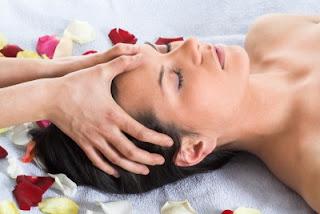 Mujer recostada recibiendo masaje en la cabeza
