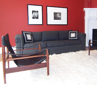 red contemporary living room with black and white artwork Swedish safari chair white Flokati rug