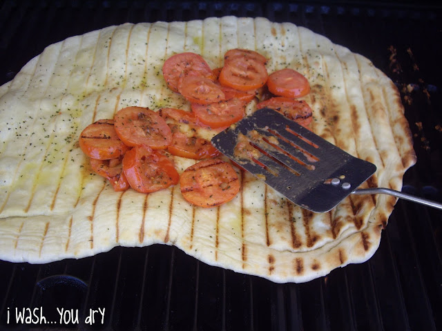 A spatula adding sliced grilled tomatoes on top of a grilled pizza crust.