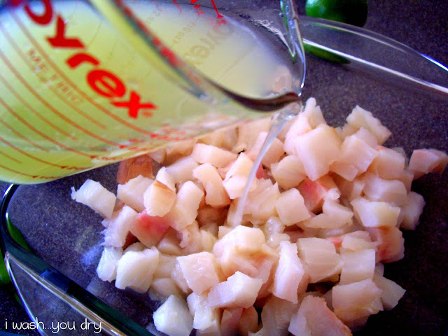 Lime juice being poured on top of a dish of raw chopped halibut.