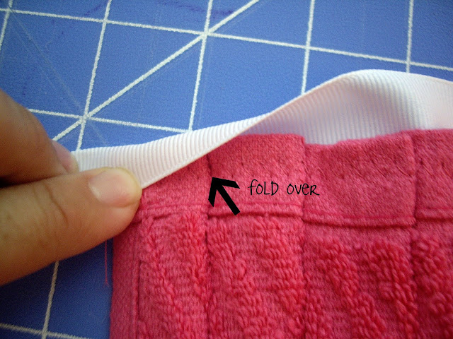 A finger folding over the edge of a ribbon onto the back of the dishtowel apron.