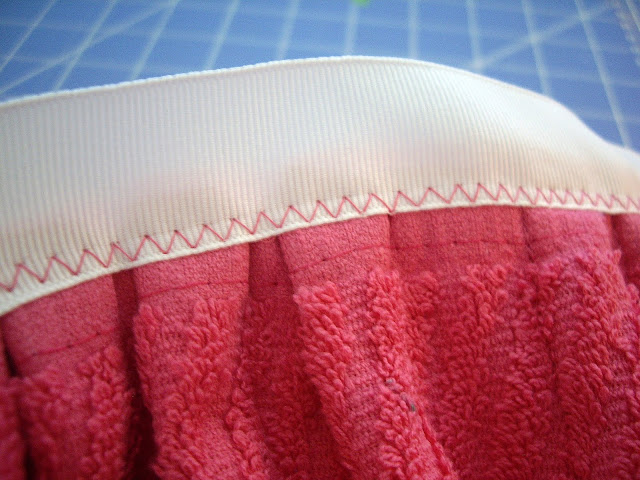 A ribbon sewed onto the top of a dish towel apron.