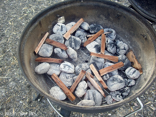 A barbecue with coals and mesquite sticks.