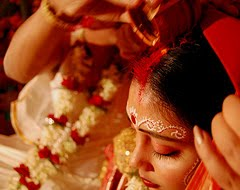 Indian bride-groom applying sindoor on bride's hair parting