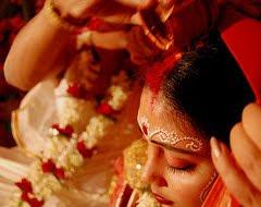 Indian bride-groom applying sindoor on bride's hair parting