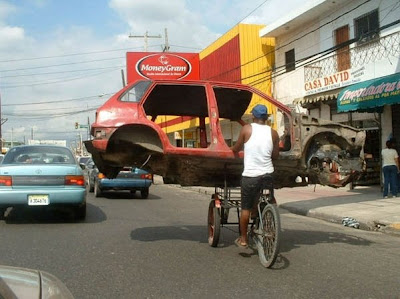 hombre en bicicleta tres ruedas transportando chasis de coche Man on bicycle three wheels carrying car chassis