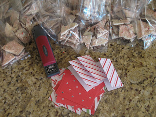 Using small pieces of festive paper and a stapler, assemble mini notes for bags of peppermint bark.