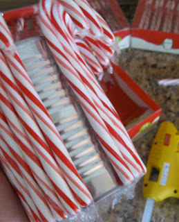 Glue the candy canes around the entire outside of the aluminum can.