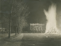 A black and white photograph of a bonfire on a lawn.