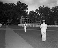 A black and white photograph of men in uniform on the lawn.