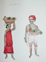 "A watercolor illustration showing two figures. On the left is a woman in gold jewelry and red clothing, balancing a basket on her head. On the right is a man wearing white and red shorts, and a red headpiece or turban. He is holding a knife and a basket. The handwritten caption reads ""Gardener."""