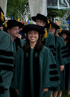 A color photograph of several people in Dartmouth Ph.D. gowns, which are green and black. A smiling young woman is in the center of the photograph.